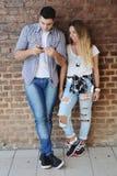 使用智能手机的年轻夫妇 库存图片