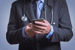 使用智能手机的医生做病历 免版税库存图片