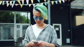 使用智能手机触摸屏的俏丽的亚裔低劣的女孩画象户外 股票视频