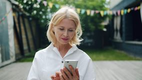 使用智能手机触摸屏的美丽的成熟妇女户外 影视素材