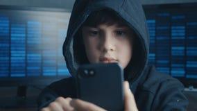使用智能手机设备的年轻戴头巾男孩 天才男孩奇迹画象乱砍系统在网际空间 股票视频
