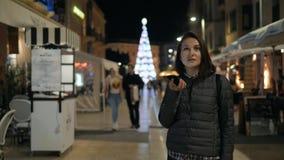 使用智能手机语音识别的女孩,口授想法,在夜晚上街道,学生的声音拨的消息 股票视频