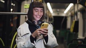 使用智能手机身分的愉快的年轻女人画象在公共交通工具 城市光背景 影视素材