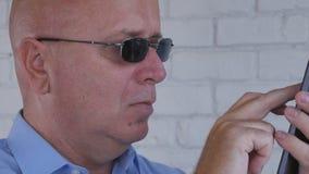 使用智能手机通信,商人佩带的太阳镜发短信 免版税库存照片