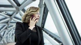 使用智能手机通勤者的可爱的白肤金发的女商人在城市,俏丽的年轻女商人谈话由电话反对 股票视频
