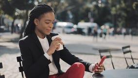使用智能手机饮用的咖啡的时髦的非洲的女商人坐在舒适咖啡馆的夏天大阳台 企业夫人 股票视频