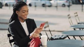 使用智能手机饮用的咖啡的时髦的非洲的女商人坐在舒适咖啡馆的夏天大阳台 ?? 影视素材