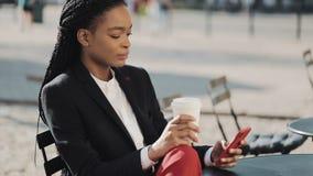 使用智能手机饮用的咖啡的时髦的非洲的女商人坐在舒适咖啡馆的夏天大阳台 ?? 股票录像