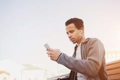 使用智能手机,体育的制服和耳机人听到音乐 免版税库存图片
