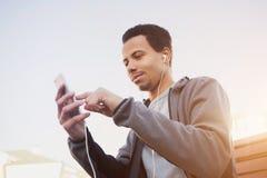使用智能手机,体育的制服和耳机人听到音乐 库存照片