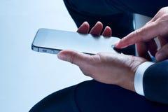 使用智能手机,商人悠闲坐 库存图片