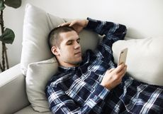 使用智能手机,困厄的人在长沙发放置了 库存图片