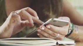 使用智能手机,在咖啡馆的饮用的咖啡的年轻,俏丽的女实业家在城市 图库摄影