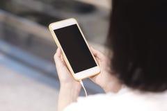 使用智能手机,在智能手机的拷贝空间的妇女 免版税库存照片