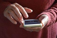 使用智能手机,在触摸屏幕的手指的妇女 免版税库存照片