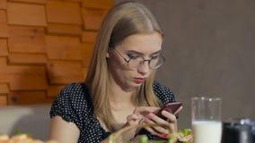 使用智能手机,坐在餐馆的一个女孩使用互联网 影视素材