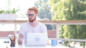 使用智能手机,坐在utdoor办公室,红色头发 图库摄影