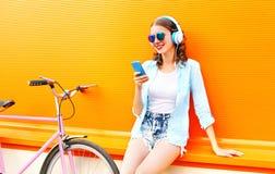 使用智能手机,夏天少妇听到音乐 免版税图库摄影