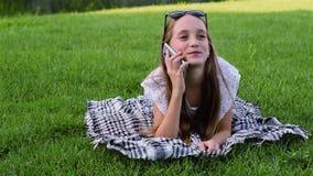 使用智能手机,夏天礼服的美丽的女孩在草说谎在公园, 股票视频