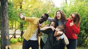 使用智能手机,嬉戏的青年男人和妇女采取selfie在公园,做滑稽的面孔并且戴太阳镜 库存照片
