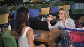 使用智能手机,少妇拍她的购物中心的朋友照片  免版税库存照片