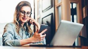 使用智能手机,年轻女实业家在咖啡店坐在计算机和笔记本前面的桌上, 束起通信有概念的交谈媒体人社交 免版税库存图片