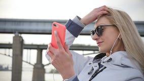 使用智能手机,年轻美丽的金发碧眼的女人做selfie 年轻女人享受沿河的堤防的步行 股票录像