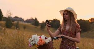 使用智能手机,有一辆自行车的女孩在帽子做一selfie 股票录像
