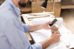使用智能手机,被集中的木工传送信息 免版税库存图片