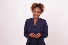 使用智能手机-黑peopl的非裔美国人的女商人 免版税库存图片