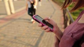 使用智能手机app,浏览互联网的时髦行家女孩的手,发短信和沟通 户外 股票视频