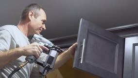 使用曲头钉钉子气枪的建筑工人加冠铸造在构筑修剪的白色厨房壁柜, 股票录像