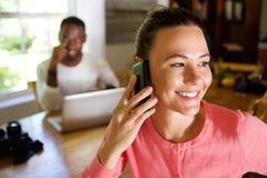 使用有一个人的妇女手机在背景 免版税库存照片