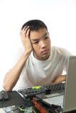 使用有乏味面孔的亚裔少年计算机 库存照片