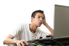 使用有乏味面孔的亚裔少年计算机 图库摄影