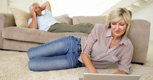 使用有伙伴的妇女膝上型计算机谈话在长沙发的电话 股票视频