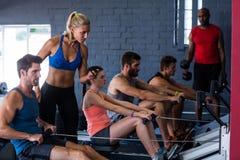使用有健身辅导员的人们划船器在健身房 库存图片
