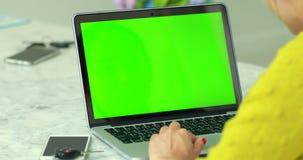 使用有关键绿色屏幕的妇女膝上型计算机 股票视频