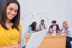 使用有创造性的队的妇女膝上型计算机工作在她后 库存图片