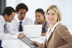 使用有办公室会议的女性执行委员画象片剂计算机在背景 库存图片