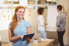 使用有同事的微笑的女实业家数字式片剂 库存图片