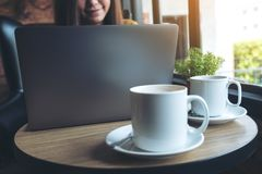 使用有咖啡杯的一名美丽的亚裔妇女膝上型计算机在木桌上在咖啡馆 免版税库存照片
