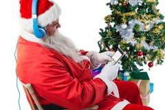 使用有圣诞树和礼物的圣诞老人一个手机 免版税库存照片