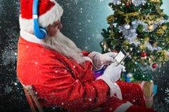 使用有圣诞树的圣诞老人的综合图象手机 库存照片