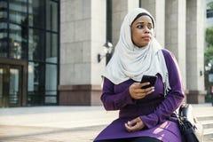 使用有失望的伊斯兰教的妇女电话 免版税库存图片
