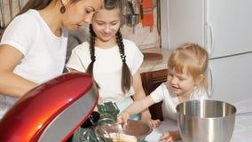 使用有她的两个女儿的,搅拌器妈妈烹调蛋糕的奶油 股票录像