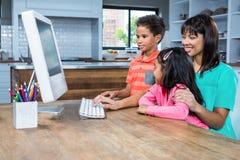 使用有她的孩子的愉快的母亲计算机 库存照片