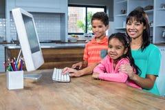 使用有她的孩子的愉快的母亲计算机 库存图片