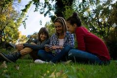 使用有她的少年孩子的愉快的母亲手机本质上 免版税库存图片