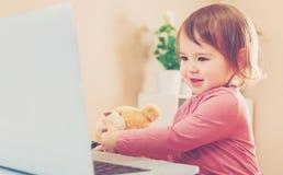 使用有她的玩具熊的小孩女孩一台膝上型计算机 免版税库存照片